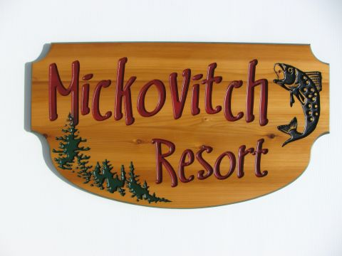 Engraved wooden sign with trees and fish