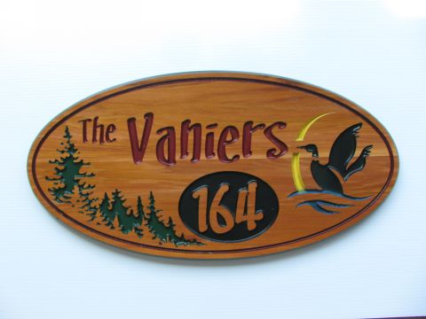 Oval routered wooden sign with address, trees and loon